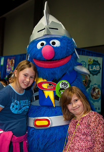 Amelia (age 9) and Samantha (7) from Takoma Park MD pose with Super Grover of Sesame St. and PBS Kids.