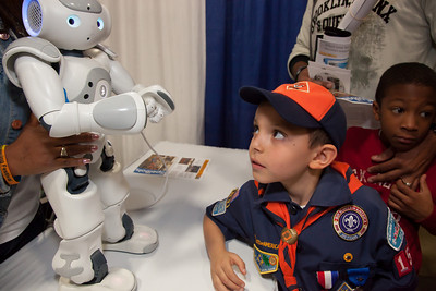 Ibrahim Omeish (age 7) of Fairfax VA looks at a robotic pet designed and manufactured by Sony.