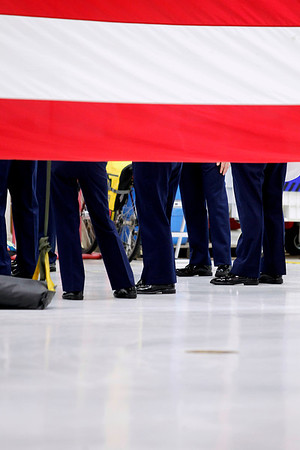 Record-Eagle/Jan-Michael Stump<br /> U.S. Coast Guard crew members wait behind a large American flag before the start of Friday's Change of Command Ceremony as Cmdr Joseph Buzzella, Jr. relieves Cmdr Jonathan Spaner as head of U.S. Coast Guard Air Station Traverse City Friday in the station's hanger.