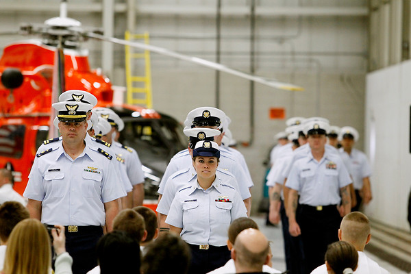 Record-Eagle/Jan-Michael Stump<br /> U.S. Coast Guard Air Station Traverse City crew members make their way into the hangar for the start of Friday's Change of Command Ceremony, as Cmdr Joseph Buzzella, Jr. relieves Cmdr Jonathan Spaner as head of the station.