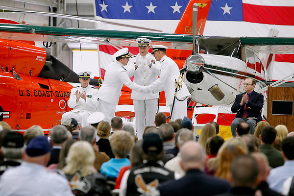 Record-Eagle/Jan-Michael Stump<br /> Cmdr Jonathan Spaner, left, and Cmdr Joseph Buzzella, Jr. shake hands as Rear Admiral Michael Parks applauds during Friday's Change of Command Ceremony at U.S. Coast Guard Air Station Traverse City.