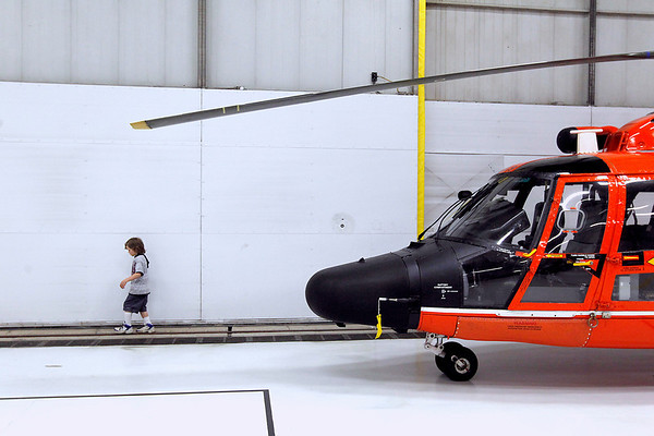 Record-Eagle/Jan-Michael Stump<br /> Rowan Schultz, 7, balances himself as he walks along the track for hangar doors at Air Station Traverse City before the start of Friday's Change of Command Ceremony.