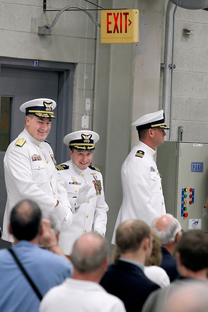 Record-Eagle/Jan-Michael Stump<br /> U.S. Coast Guard Rear Admiral Michael Parks, left, Cmdr Jonathan Spaner, center, and Cmdr Joseph Buzzella, Jr. wait to enter Friday's Change of Command ceremony in the station's hanger. Buzzella is replacing Spanner as head of the station.