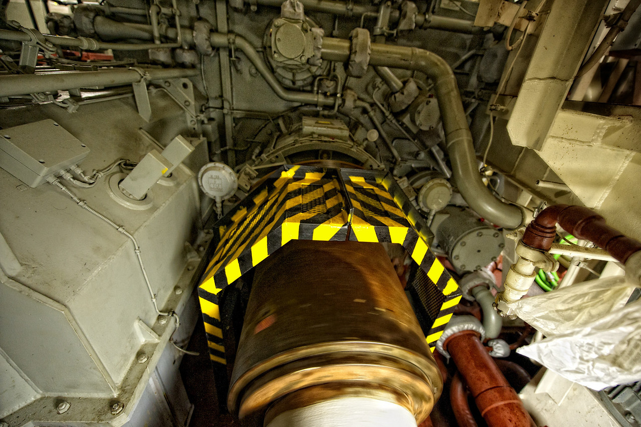 One of the two propeller shafts spinning through the center of the engine room.