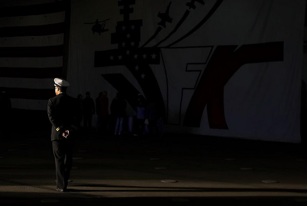 A Navy officer stands in a shaft of light on board the USS John. F. Kennedy.  Saturday, March 2, 2007
