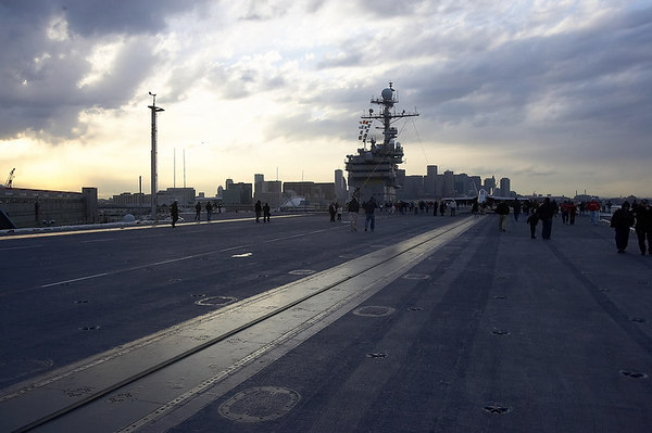 The flight deck of the USS JFK with the city in the background