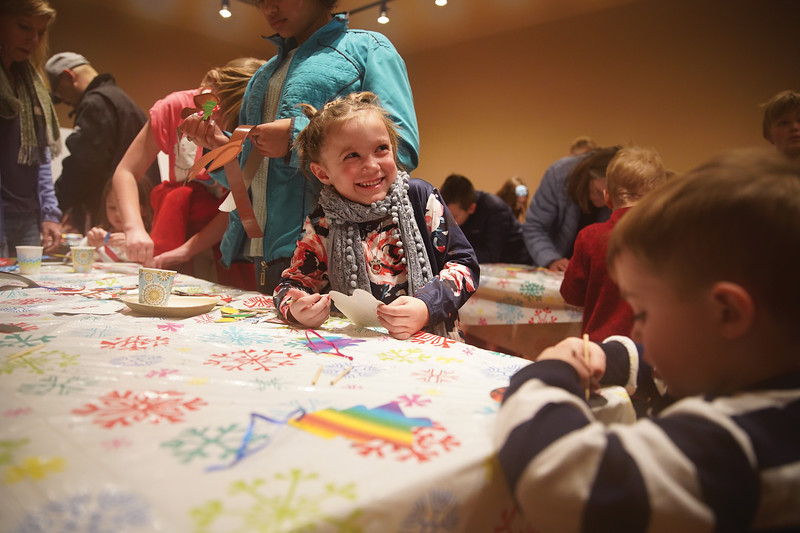 Matthew Gaston | The Sheridan Press<br>Addy Cooley, 5, smiles at her parents while making Christmas decorations during the Ucross Community Christmas Saturday, Dec. 14, 2019.