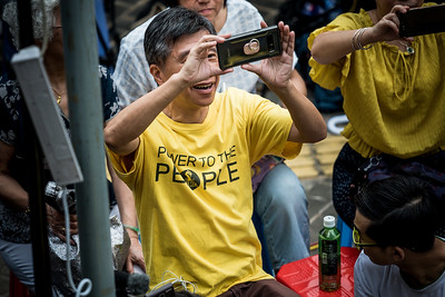A participant documents the speeches at an event commemorating the 4th anniversary of the Umbrella Revolution in Hong Kong on September 28, 2018.