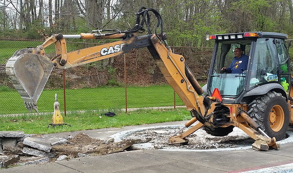 Harold Taylor operates a backhoe to break up the concrete in the area of the former kiddie pools at Cascade Park. The pools are to be removed in the United Way's restoration plans, with a shallow end for young children included in the proposed single park pool.