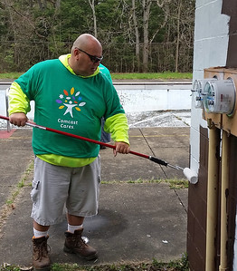 Comcast volunteer Mark Painter whitewashes the exterior of the Cascade Park pool bath house.