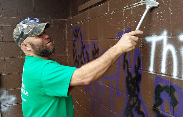 Comcast volunteer Larry Smith scrapes loose paint from the block walls of the Cascade Park pool bath house in preparation for whitewashing.