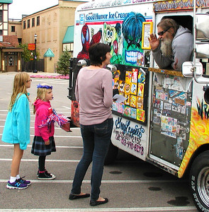 Debbie Blank | The Herald-Tribune Jen Saner, Batesville, buys treats for her daughters from the Biker Dude Ice Cream truck after the group photo.