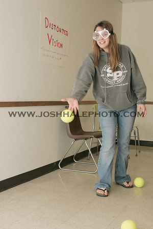 Sami Bingaman tries to throw a ball while wearing distortion goggles for the Psychology Club open house on Saturday, April 22, 2006.