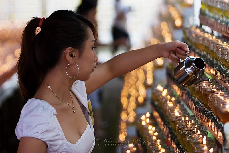 A helper refilling oil lamps.