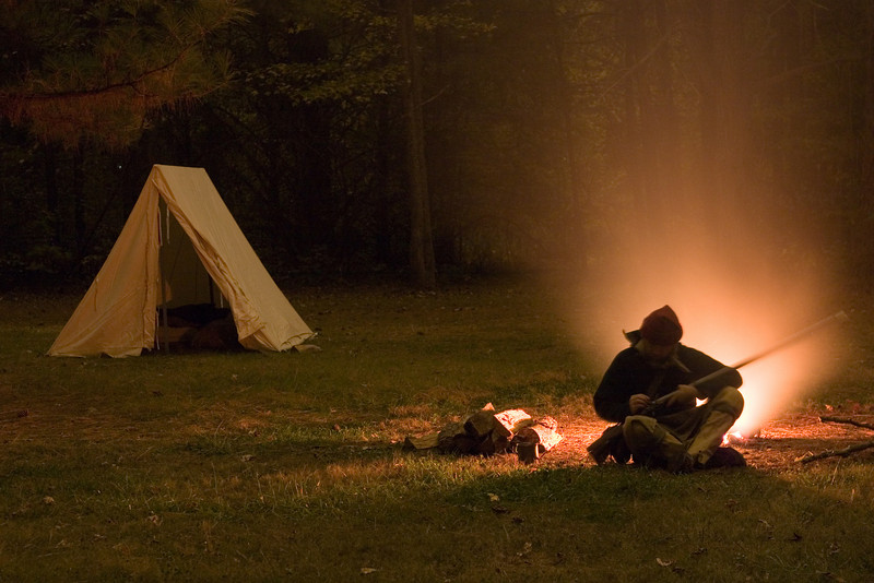 A colonial rifleman in front of his campfire, working on his firelock.