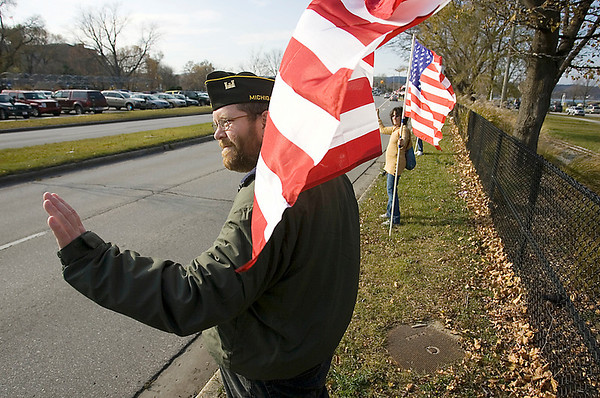 """Record-Eagle/Keith King<br /> Kevin Deeren, of Interlochen, alongside his wife, Linda Deeren, waves to passing motorists Thursday, November 11, 2010 along Grandview Parkway. Kevin, a United States Army veteran who served in Iraq, also has a son in the United States Army Reserve who is serving in Afghanistan. """"She's the real hero,"""" Kevin said about his wife Linda, """"An Army wife and an Army mother."""""""