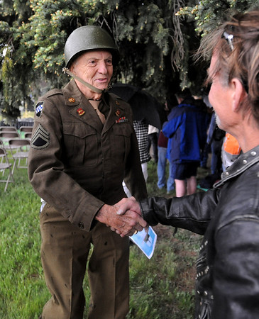"""WWII veteran, Stewart Boone, 85, still fits in his uniform. He shakes the hand of a guest at the ceremony.  He said he weighs 5 more pounds than he did when he was in the military. Boone recieved a Bronze Star.<br /> The Vietnam Memorial Arch, honoring Boulder County military members who lost their lives in Vietnam, was dedicated in a ceremony at Mountain View Cemetery in Boulder on May 29th, 2010.<br /> For more photos, go to  <a href=""""http://www.dailycamera.com"""">http://www.dailycamera.com</a>.<br /> Cliff Grassmick / May 29, 2010"""