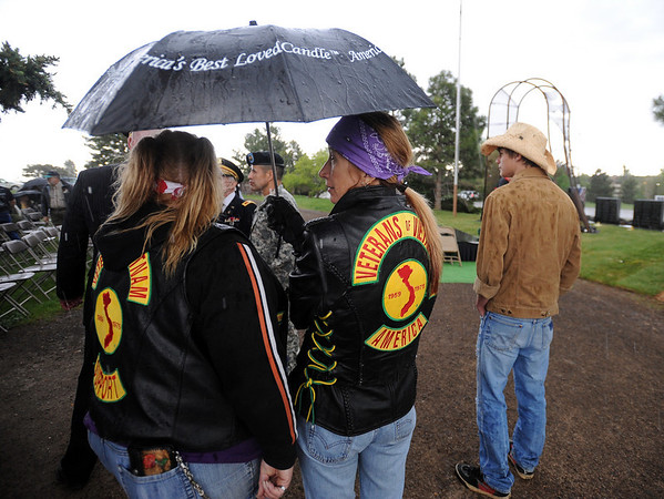 """Lady Shay, left, and Libby Ice Pick wait out the rain at the arch. The ceremony was moved inside later in the evening.<br /> The Vietnam Memorial Arch, honoring Boulder County military members who lost their lives in Vietnam, was dedicated in a ceremony at Mountain View Cemetery in Boulder on May 29th, 2010.<br /> For more photos, go to  <a href=""""http://www.dailycamera.com"""">http://www.dailycamera.com</a>.<br /> Cliff Grassmick / May 29, 2010"""