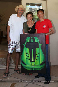 Sanjar and Sheri present Maurice with the original painting by Sheri of Maurice's car.