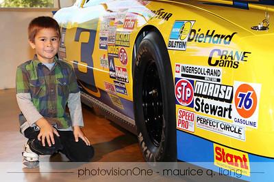 AJ poses with a race car.