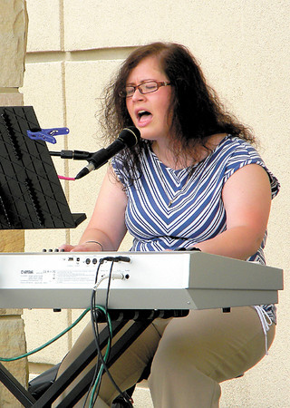 Dr. Michelle Miller sings while the offering is taken at the crusade. — Dan Irwin