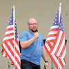 Framed by flags attached to a worshipper's chair, the Rev. Mark Bupp of City Reach Church talks about his congregation's plans to evangelize New Castle. — Dan Irwin