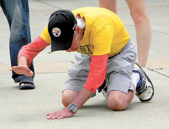 'Mitch,' a passer-by who joined the crusade at the invitation of the Rev. Randy Crum, falls to his knees to pray.  — Dan Irwin