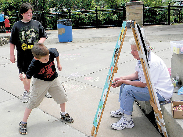 Chance Jones, 7, gets ready to fling as he plays a toss game prior to the start of Saturday's Vision Ministries crusade at Riverwalk Park. Watching him are Brandon Vogel, 11, and Hope Cummins.<br />  — Dan Irwin