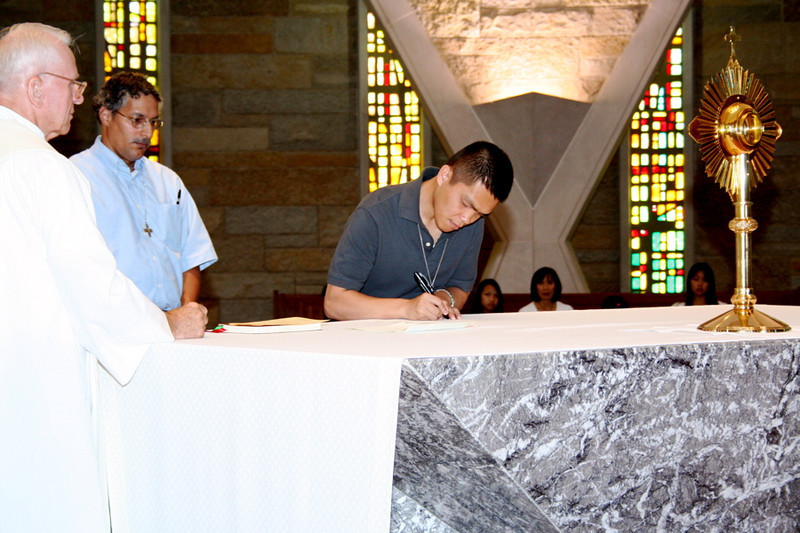 Br. Long signs his papers.