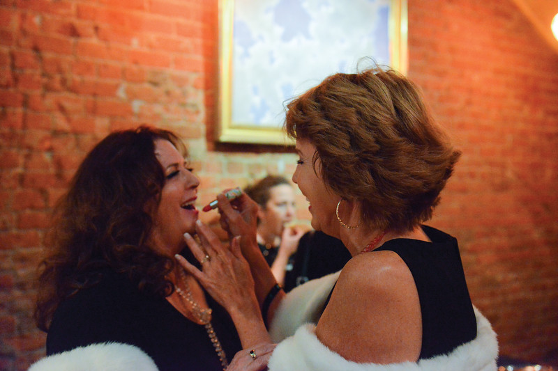 "Ashleigh Fox | The Sheridan Press<br /> <br /> Nancy Jo Wesmitzer receives help putting on lipstick from her sister, Jean Speigelberg, ahead of the WYO Theater 2017 Gala performance of ""Sister Act"" on Saturday night."