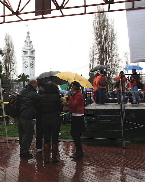 Staff huddle behind the stage, with Ferry Building tower in background.
