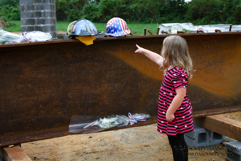 A young girls recognizes the helmets on display of fallen figherfighters before the 9-11 ceremony starts