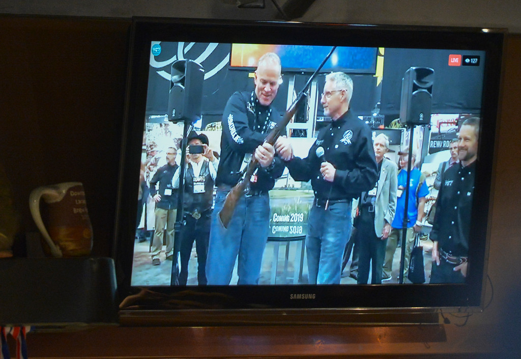 Justin Sheely | The Sheridan Press<br /> <br /> Wyoming Governor Matt Mead, left, is presented with a Weatherby rifle by Ed Weatherby shown via Facebook Live on a screen during the Project Enterprise announcement at Black Tooth Brewing Company Tuesday, Jan. 23, 2018. Adam Weatherby announced via Facebook Live plans to move his family's well-known firearms manufacturer to Sheridan, adding an additional 65-90 jobs to the community over the next several years.