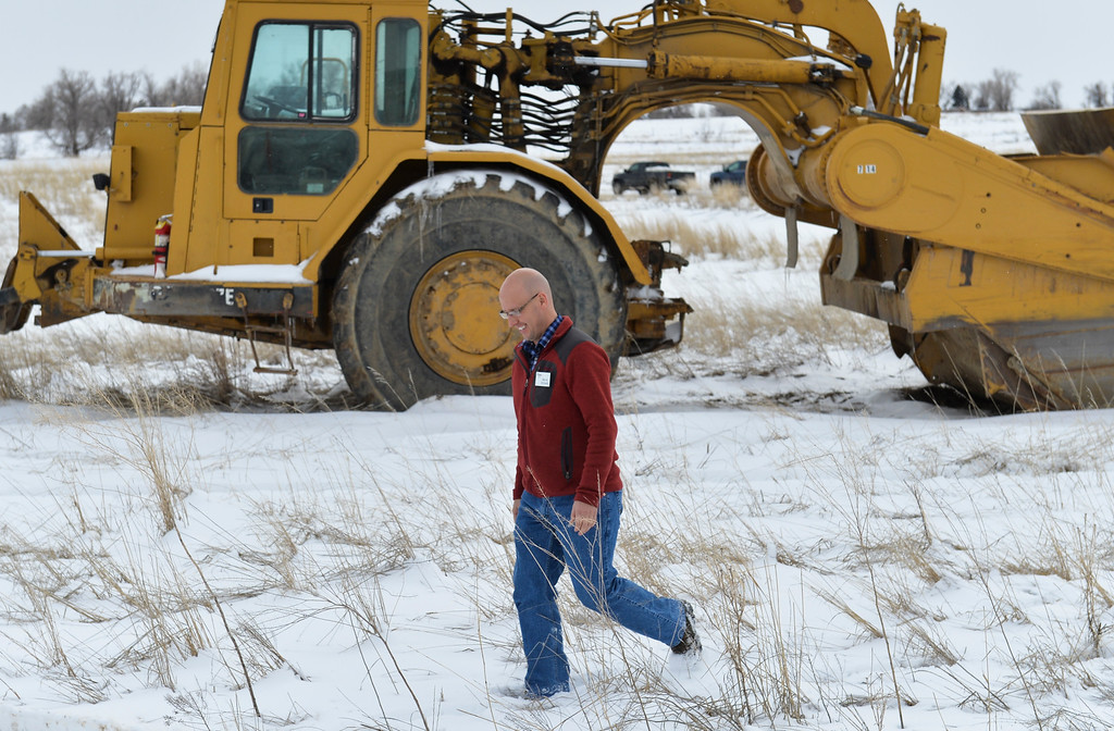 Justin Sheely   The Sheridan Press<br /> Sheridan Councilor Alex Lee walks past heavy equipment during the groundbreaking ceremony at the Weatherby site at High Tech Park in north Sheridan Friday, April 6, 2018.