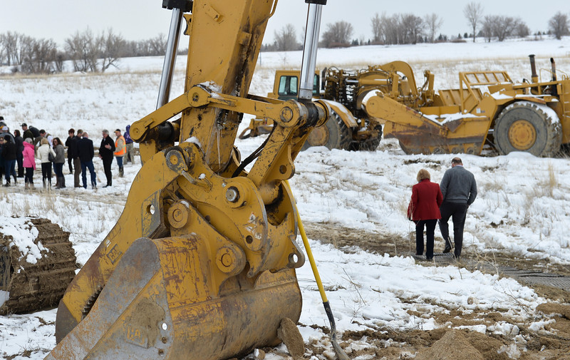 Justin Sheely | The Sheridan Press<br /> People walk past heavy equipment during the groundbreaking ceremony at the Weatherby site at High Tech Park in north Sheridan Friday, April 6, 2018.