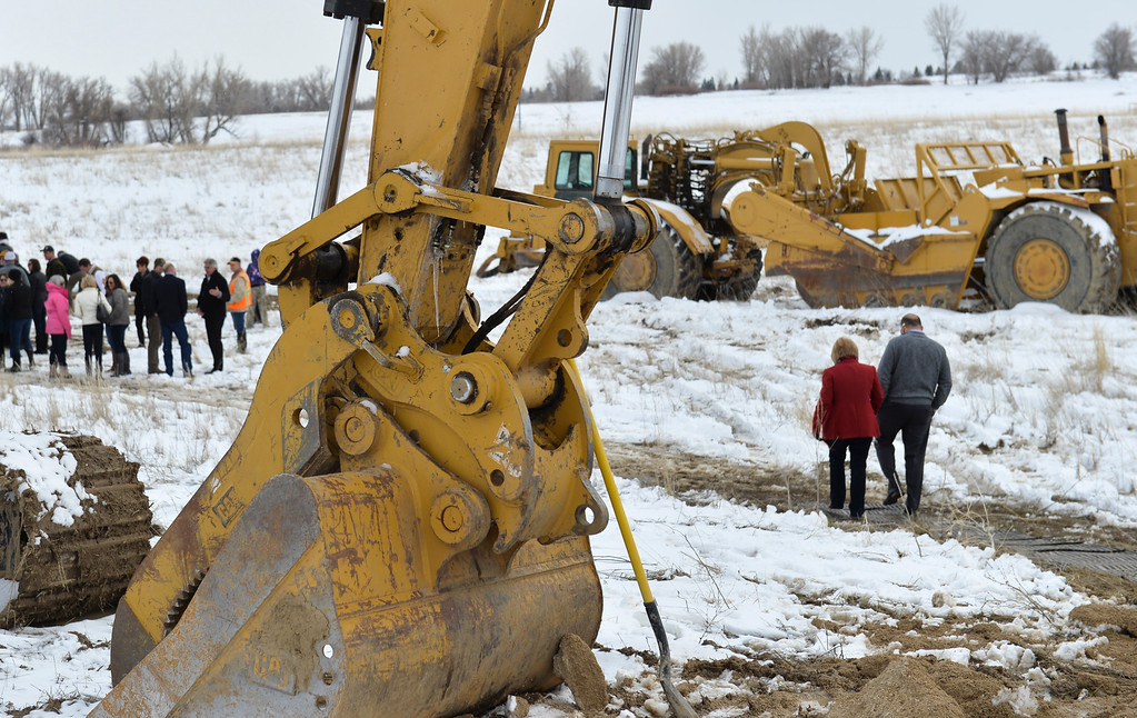 Justin Sheely   The Sheridan Press<br /> People walk past heavy equipment during the groundbreaking ceremony at the Weatherby site at High Tech Park in north Sheridan Friday, April 6, 2018.