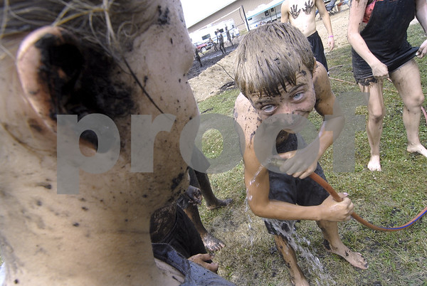 -Messenger photo by Hans Madsen<br /> <br /> DAven Rees, 12, with the Washington Winners 4-H Club, uses a garden hose Saturday morning to remove the worst of the mud he became coated with during the annual mud volleyball game at the Webster County Fair. At left, Madison Anderson, 14, also a Washington Winner, waits for her chance to among other things, wash the blob of mud out of her ear.
