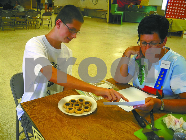 -Messenger photo by Emilie Nelson <br /> <br /> Dylan Johnson, a member of the Gowrie Groundbreakers 4-H Club, discusses his chocolate star cookies with food and nutrition judge Barb Sexton at the Webster County Fair Tuesday afternoon.