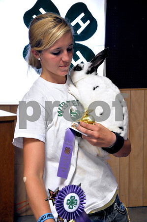 "-Messenger photo by Emilie Nelson <br /> <br /> Jenny Randleman, 18, of Gowrie, a member of the Country Charmers 4-H Club, holds her rabbit, ""Pepsi,"" after the rabbit show at the Webster County Fair Thursday afternoon. Randleman won commercial champion for her rabbits at the show."