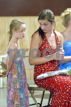 -Messenger photo by Hans Madsen<br /> <br /> Carlyn Lundberg, 5, has a moment with her older sister Mariah Welter during the 2012 Webster County Fair King and Queen selection Wednesday night. Lundberg brought her own paper crown along.