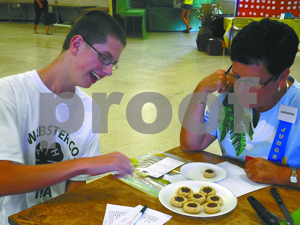 -Messenger photo by Emilie Nelson <br /> <br /> Dylan Johnson, a member of the Gowrie Groundbreakers 4-H Club, laughs as he shares his trial and error experience baking chocolate star cookies with food and nutrition judge Barb Sexton during 4-H exhibit judging at the Webster County Fair Tuesday afternoon.