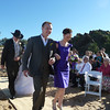 Best man and bridesmaid followed by the bride and father approaching the wedding site
