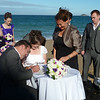 Our grandson Nathan the groom signing watched by the celebrant Fay Corbett one of the friends.