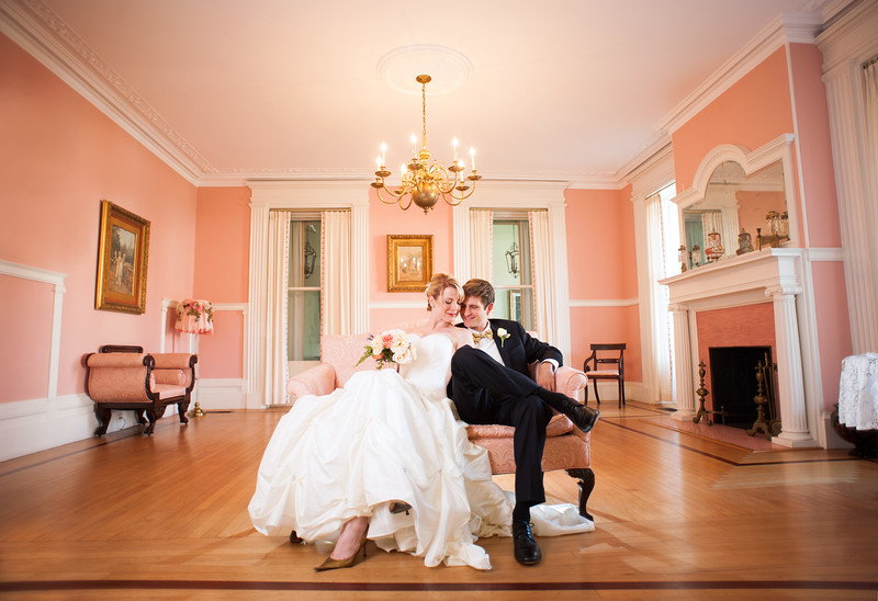 """Bride and groom sit together on loveseat in Markland House's """"Pink Room."""""""