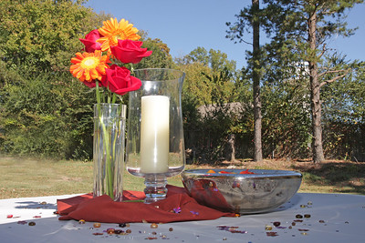 A table centerpiece with flowers, a candle, and a fancy bowl
