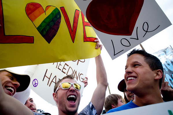 (From left to right) Tanner Ray, Cole Abshere, and Mike Manning cheer as cars honk their horns as they protest against Westboro Baptist Church in front of Boulder High School in Boulder, Thursday, April 22, 2010.
