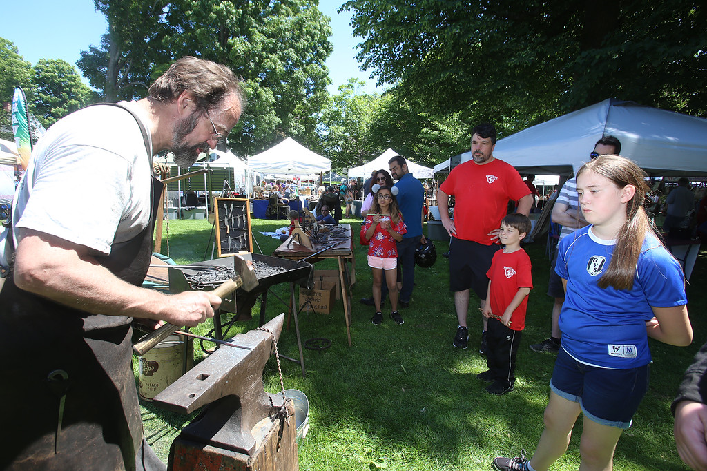 . Annual Strawberrie \'n\' Arts Festival on Westford Town Common. Blacksmith Carl West of Waltham makes a corkscrew as Ava Murray, 10, of Groveland, right, and Glen Anderson and son Kai, 6, of Westford, watch. (SUN/Julia Malakie)