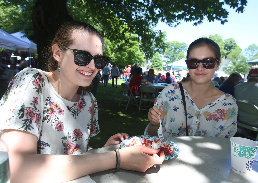 . Annual Strawberrie \'n\' Arts Festival on Westford Town Common. Miriam Jones, left, and her sister Emma Jones, both of Warwick, R.I. share strawberries and cream. (SUN/Julia Malakie)