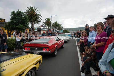 Whangamata Beach Hop 2012.Red Mustang Mach1 in parade, driving through crowd.