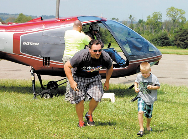 Andrew Crowl, 6, and his uncle Josh, both of New Castle, disembark from their helicopter ride at Wings and Wheels. Andrew, who was taking his second ride, said he wasn't scared, but his uncle — a first timer — was. The helicopter ride was the favorite part of Andrew's day.<br /> — Sam Luptak Jr.